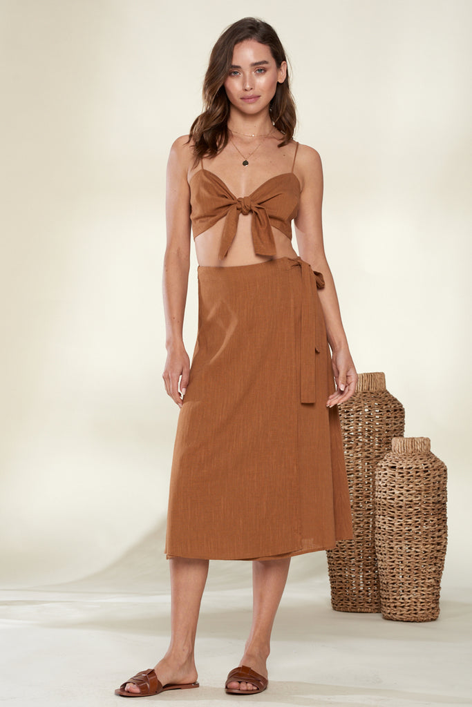 A woman wearing a brown linen front tie top and skirt two piece set.