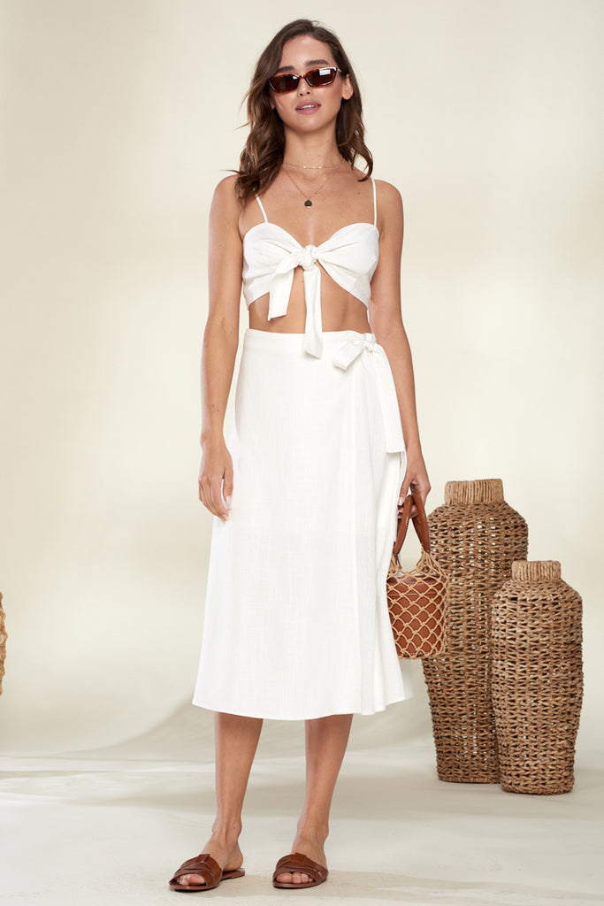 A woman wearing an ivory linen front tie top and skirt two piece set.