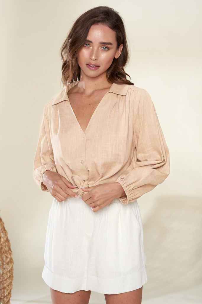 A woman wearing a sand linen button-up shirt with button front linen shorts.