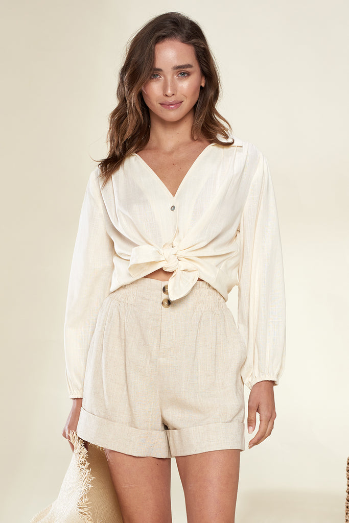 A woman wearing an ivory linen button-up shirt with button front linen shorts.