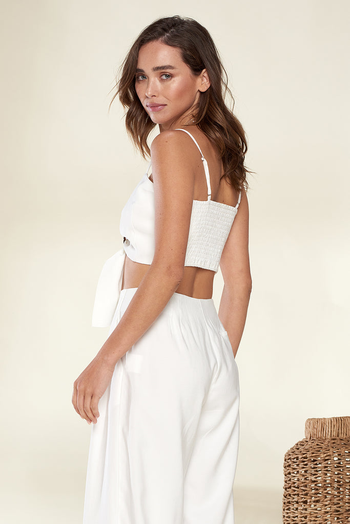 Back side of an ivory front o-ring buckle trim bandeau and wide leg pants two piece set.
