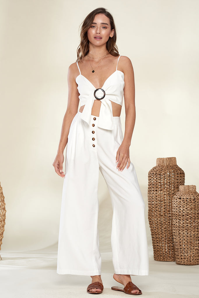 A woman wearing an ivory front o-ring buckle trim bandeau and wide leg pants two piece set.