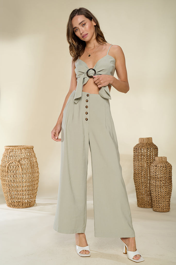 A woman wearing a sage front o-ring buckle trim bandeau and wide leg pants two piece set.