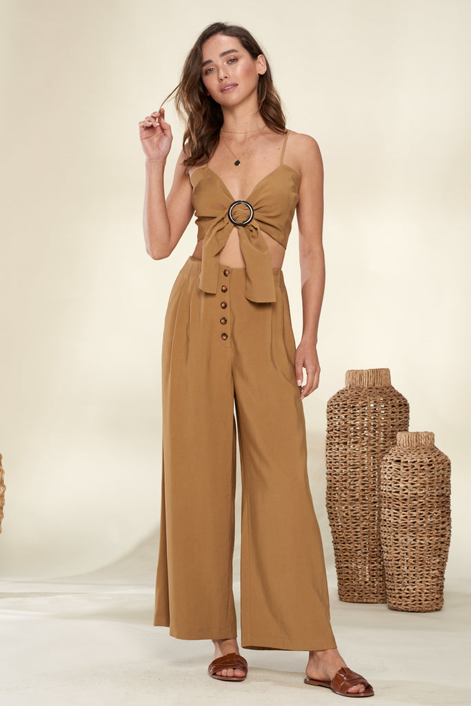 A woman wearing a khaki front o-ring buckle trim bandeau and wide leg pants two piece set.