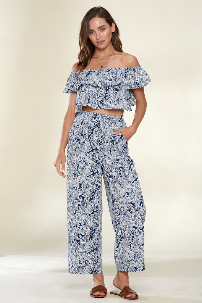 A woman wearing a navy tropical print off the shoulder ruffle detail top and cropped pants two-piece sets.