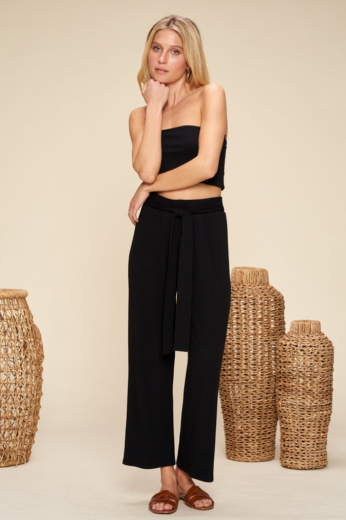 A woman wearing a black ribbed knit two piece set.