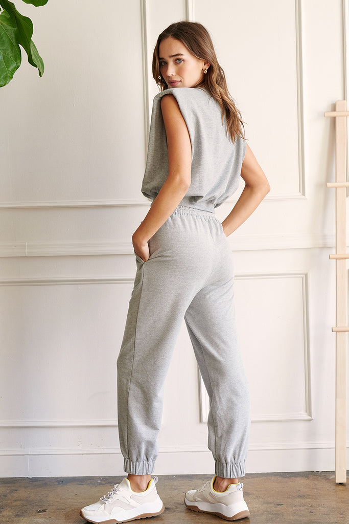 A woman wearing a heather grey padded shoulder cropped top and matching jogger sweatpants.