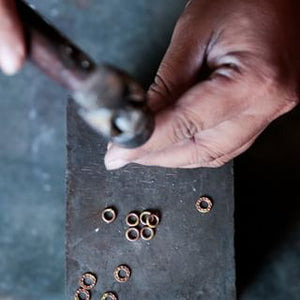 An artisan in India who makes this jewelry under fair trade practices