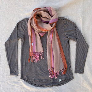 A flat lay with shirt and a fair trade and ethically made soft 100% cotton handloom scarf in a muted pink, with a lavender stripe, and coral chevron border.