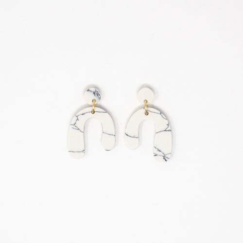 Fair trade small pretty clay earrings in an organic parabola shape; white with dark blue marbling