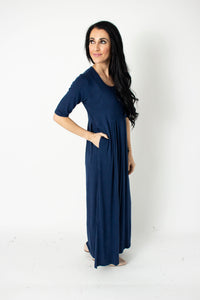 Side view of fair trade and ethical navy dark blue long maxi dress with empire waist, pleats, and pockets, in a very soft, high quality cotton knit.
