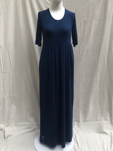 Showing on mannequin, fair trade and ethical navy dark blue long maxi dress with empire waist, pleats, and pockets, in a very soft, high quality cotton knit.