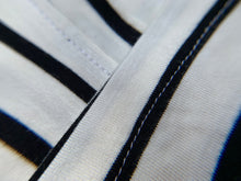 Load image into Gallery viewer, Long sleeve white and black striped soft knit shirt closeup of fabric
