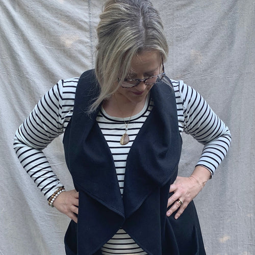 A modern black knit vest, made by a circle pattern, with pockets; ethical clothing, fair trade clothing.
