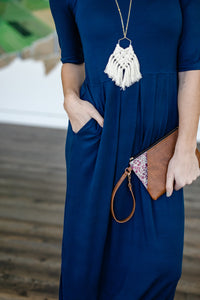 Showing pocket and waist detail of fair trade and ethical navy dark blue long maxi dress with empire waist, pleats, and pockets, in a very soft, high quality cotton knit.