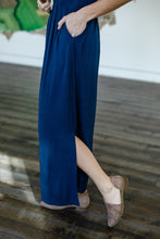 Load image into Gallery viewer, Closeup of side slit detail of fair trade and ethical navy dark blue long maxi dress with empire waist, pleats, and pockets, in a very soft, high quality cotton knit.
