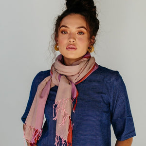 Model wearing a fair trade and ethically made soft 100% cotton handloom scarf in a muted pink, with a lavender stripe, and coral chevron border.
