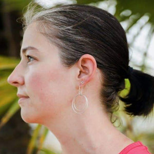 Model wearing lightweight, double circle earrings made of Alpaca silver in a fair trade cooperative near Taxco, Mexico.