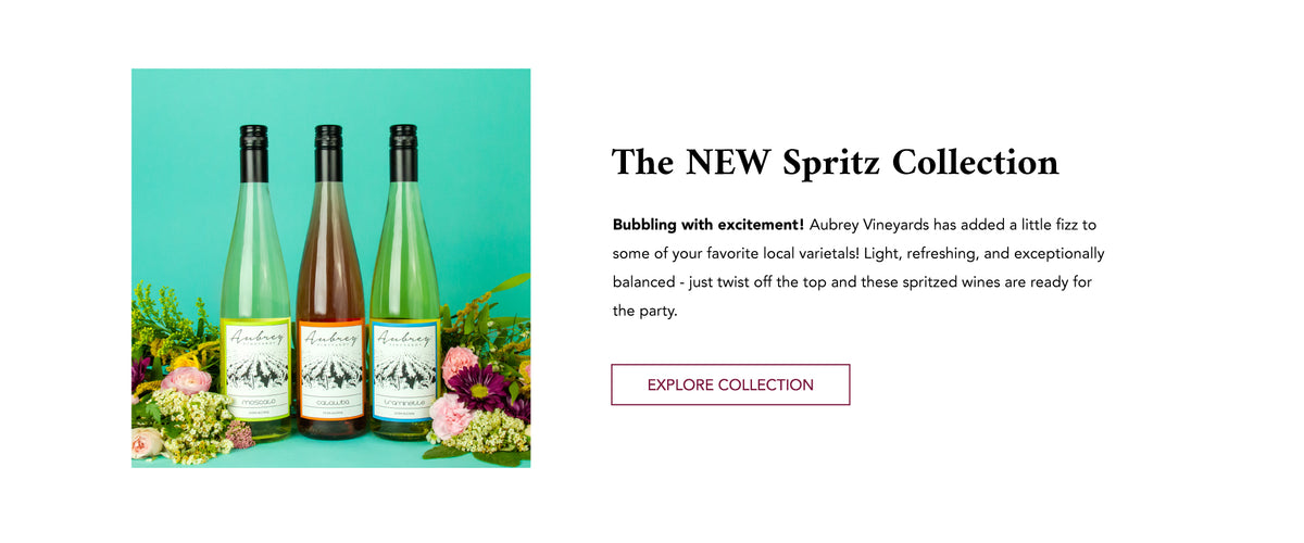 "Three bottles of wine surrounded by flowers on a blue background. Text next to the image reads, ""The NEW Spritz Collection. Bubbling with excitement! Aubrey Vineyards has added a little fizz to some of your favorite local varietals."""