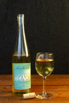 An Aubrey Vineyards wine glass sitting next to a bottle of Aubrey Vineyards Vidal Blanc