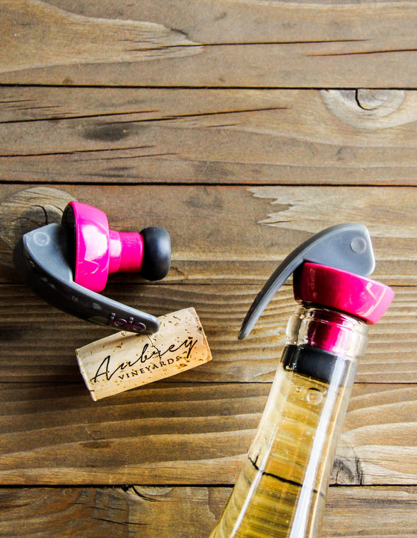 Two Joie bottle stoppers, one laying next to an Aubrey Vineyards cork and the other capping a bottle of Aubrey Vineyards wine,