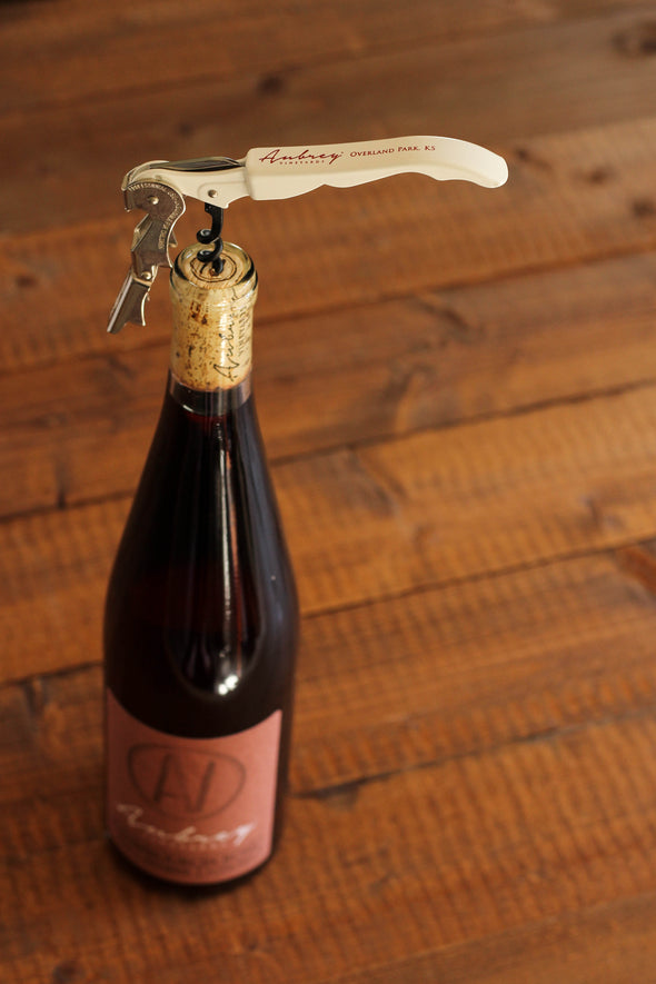 A white Aubrey Vineyards corkscrew positioned in the cork of a 2017 Chambourcin Rosé.