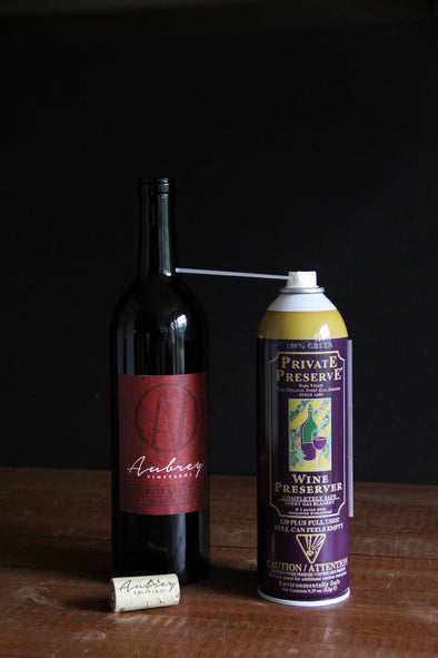 A can of Private Preserve sitting next to a bottle of Aubrey Vineyards Crimson Cabernet.