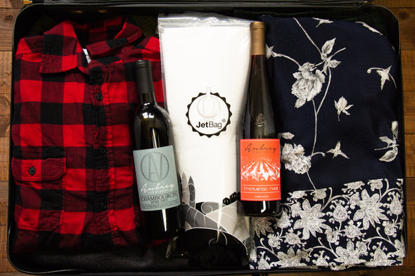 A JetBag, used to protect your wine while traveling, sits in an opened and fully packed suitcase with a bottle of Aubrey Vineyards Frontenac Rose and Aubrey Vineyards Chambourcin Semi-Dry.