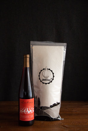 A JetBag used to protect your wine while traveling sitting behind a bottle of Aubrey Vineyards Frontenac Rosé.