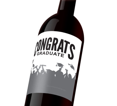 "A white wine label with silhouetted students tossing their graduation caps. The label reads, ""Congrats Graduate""."