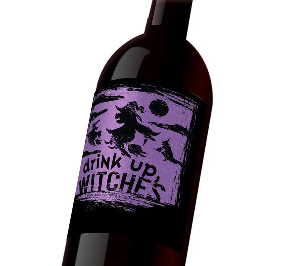 "A black and purple Halloween wine label depicting witches on their brooms in the night sky. The label reads, ""Drink Up, Witches"""