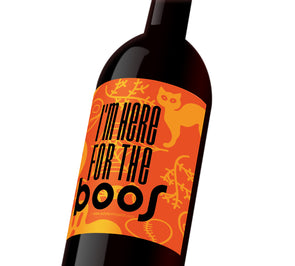 "An orange Halloween wine label with cats, ghosts, and spiderwebs that reads, ""I'm here for the boos""."