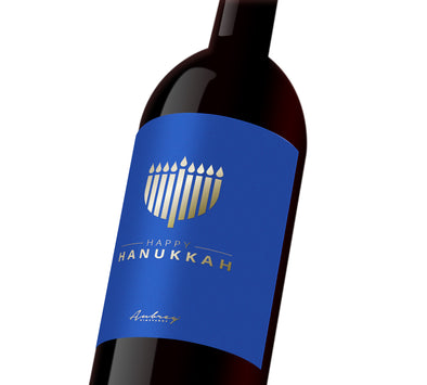 "A blue custom wine label with a silver Menorah that reads, ""Happy Hanukkah""."