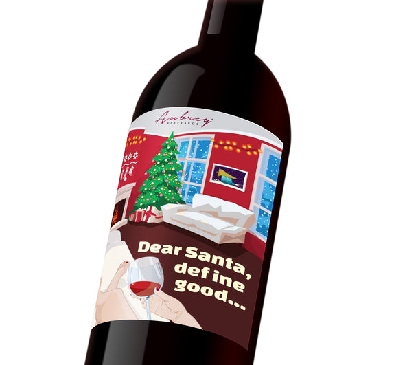 "A holiday wine label with the illustration of a woman sitting on the couch, glass of wine in hand, looking at her Christmas tree. The label reads, ""Dear Santa, Define good...."""