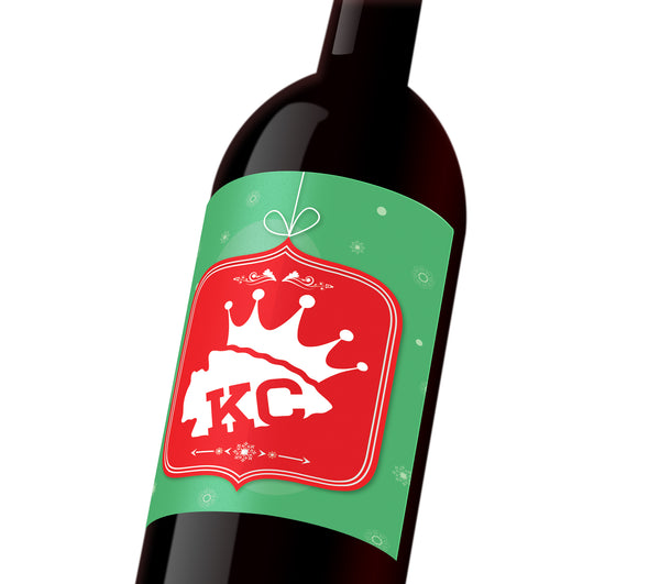 A green holiday custom wine label with a red holiday ornament depicting a white KC Chiefs spearhead wearing a KC Royals crown.