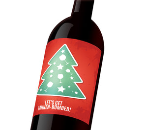 "A red holiday custom wine label with a green tree decorated with stars and wine glasses. The label reads, ""Let's get Tannen-bombed!"""