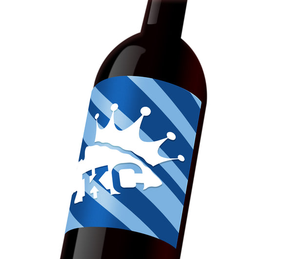 "A dark and light blue striped custom wine label with a white Chiefs spearhead that reads, ""KC"" wearing a Royals crown"