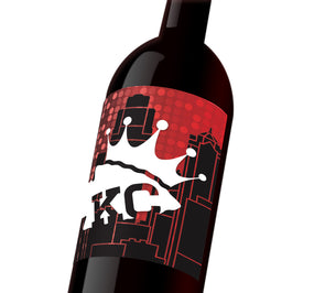 "A red custom wine label with the KC skyline in the behind a white KC Chiefs spearhead that reads, ""KC, wearing a KC Royals crown."