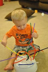 little boy playing with pipe cleaners and a colander
