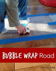 Kid Playing with bubble wrap and a toy car