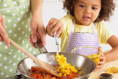 Girl cooking with her mom.