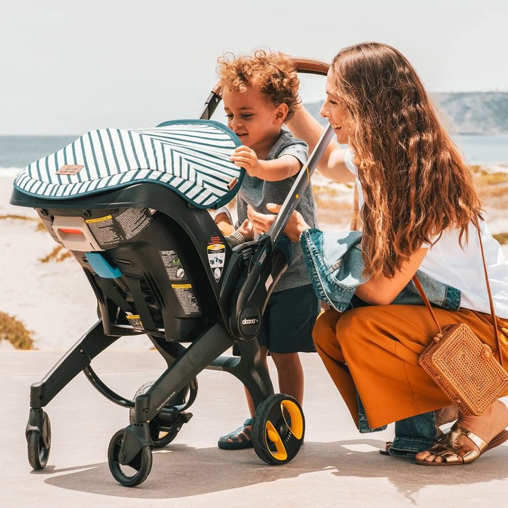 Family at the beach with their Doona stroller.