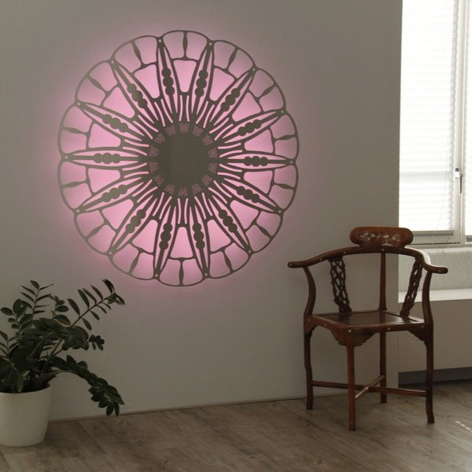 KuvaLight Anemone in aluminium with a pink color light behind it in a home setting.