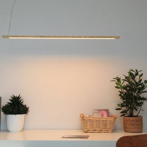 KuvaLight Line in Bamboo hanging above a desk. The color of the light can be adjusted from warm white to energizing cool white light and is also dimmable.