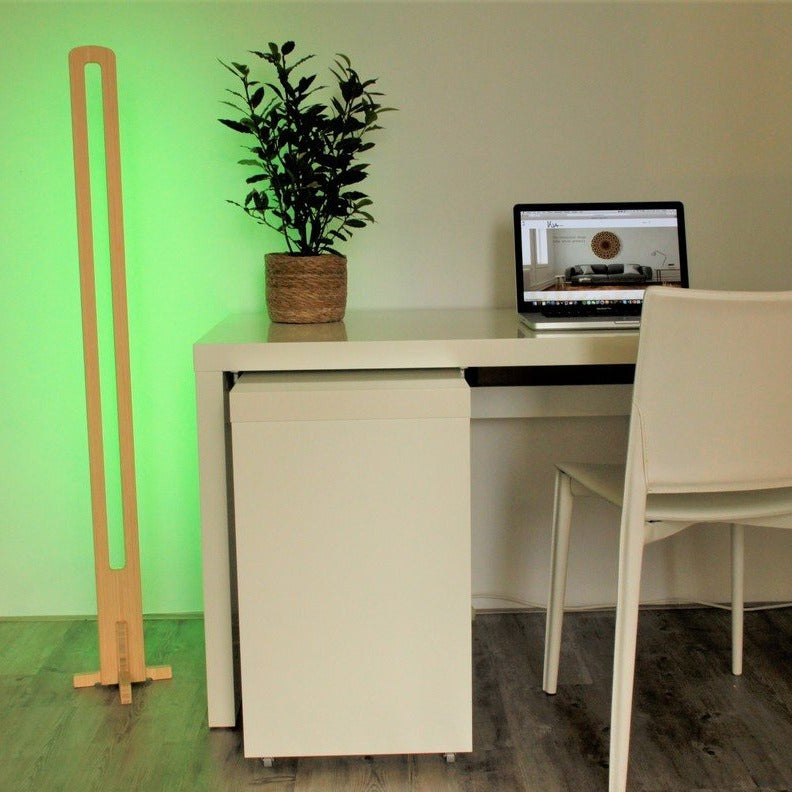 KuvaLight Parallel in Bamboo with a green relaxing light standing next to a desk.