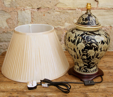 """The Antique Ceramic Lamp comes in a dark navy blue colour with a stone flowered embossed design on a wooden base and a dark cream pleated shade. It's part of the regal ceramic embossed range.   If you're looking to add a unique traditional touch to your living space, then our high quality Antique Ceramic Lamp is perfect for you. Your distinctive, high quality taste in home decor will be absolutely satisfied with this gorgeous glazed ceramic table lamp.  Set the mood right in any room but we suggest the lamp is best displayed on a console table in the hallway, on each side of the bed or on your office desk.  This statement piece is coated with a glazed, glossy finish for a long lasting shine.    """"Make your home the most beautiful place on earth, one step at a time."""""""