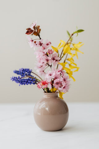 A light brown vase with a shiny finish supporting a colourful flower arrangement. The vase is sitting on a white counterto and agains a plain white wall which makes the flowers stand out. Cerulien, Home decor, How to choose the perfect vase for your flower arrangements.