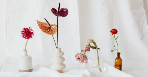A collection of four vases in very different shapes and sizes, all supporting lovely long-stemmed flowers. All four vases are displayed on a white piece of cloth resembling linen. The surrounding walls are also covered with a similar linen looking fabric  adding to the overall coziness of the picture. A bright light is shining from the left hand corener of the picture putting all items well in display. Cerulien, Home decor to fall in love with. How to choose the perfect vase for your flower arrangement blog.