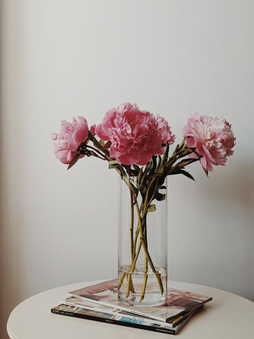 A classic column vase made of transparent glass in which beautiful pink lilies are displayed. The vase is sitting on a pile of 3 magazines piled up on a small round table against a neutral off white wall. The tone of the picture is very monochromatic and the light comes from the left hand side. Cerulien Home decor inspirations.