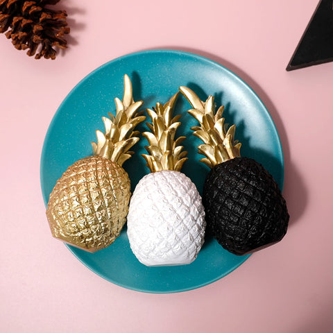 Do pineapples make you go banana? Do you know a pineapple lover? Then look no further! Our Golden Pineapple Ornament is what you've been looking for.  A stunning fruit shaped ornament topped with golden leaves, this high quality item is guaranteed to draw attention and upgrade the look of any room at home.   This stylish piece of homeware will add character and a touch of luxury to your space. Use it as a centrepiece on your table, or mix and match the sizes and colours and display them on a sideboard or shelves.  Our pineapple home decor item comes in a choice of three different colours and the leaves on top are finished with a shiny gold coloured glaze for glamour.